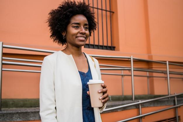 通りで屋外に立っている間コーヒーを保持しているアフロビジネス女性の肖像画。ビジネスと都市のコンセプト。 無料写真