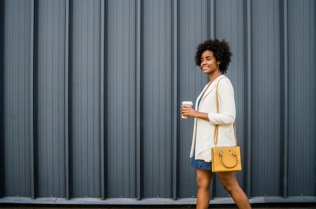 通りを屋外で歩きながらコーヒーを持っているアフロビジネス女性の肖像画。ビジネスと都市のコンセプト。 無料写真
