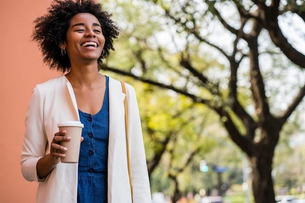 路上で屋外に立っている間笑顔でコーヒーを持ってアフロビジネス女性の肖像画。ビジネスと都市のコンセプト。 無料写真
