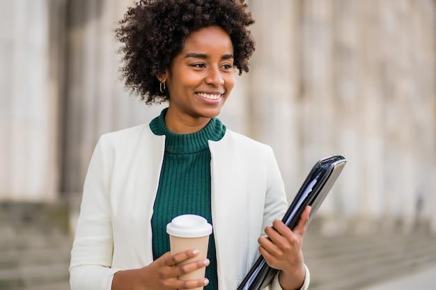 通りで屋外を歩いている間、コーヒーとクリップボードを持っているアフロ実業家の肖像画。ビジネスと都市のコンセプト。 無料写真