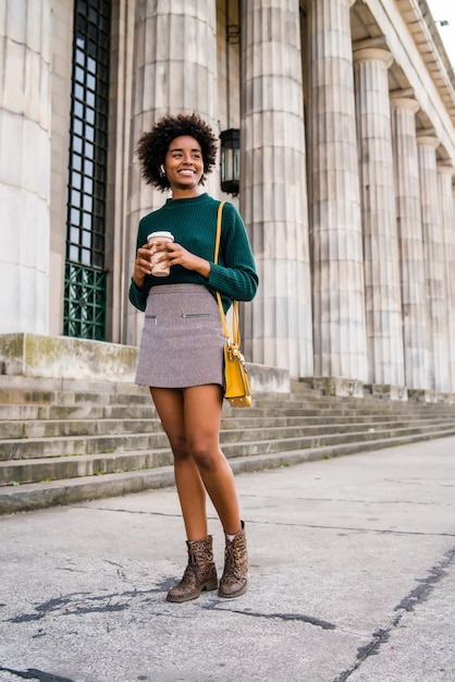 通りで屋外を歩いている間コーヒーを保持しているアフロ実業家の肖像画。ビジネスと都市のコンセプト。 無料写真