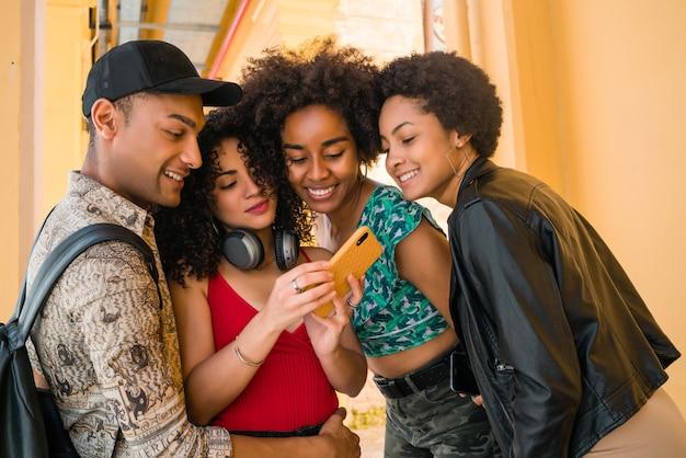 Портрет афро-друзей, весело проводящих время в городе, используя свой мобильный телефон. концепция дружбы и образа жизни. Premium Фотографии