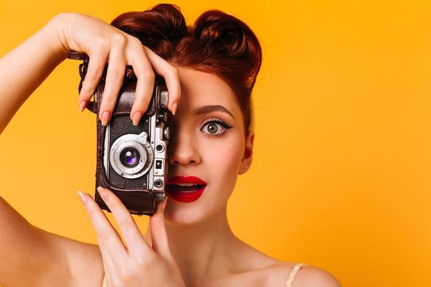 カメラを持つ驚いたピンナップ女性の肖像画。写真を撮る赤い唇を持つ魅力的な写真家。 無料写真