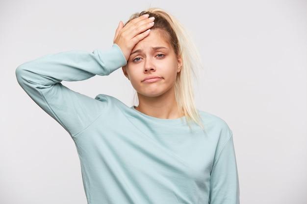 Портрет забавной милой молодой женщины со светлыми волосами и хвостом в синей футболке Бесплатные Фотографии