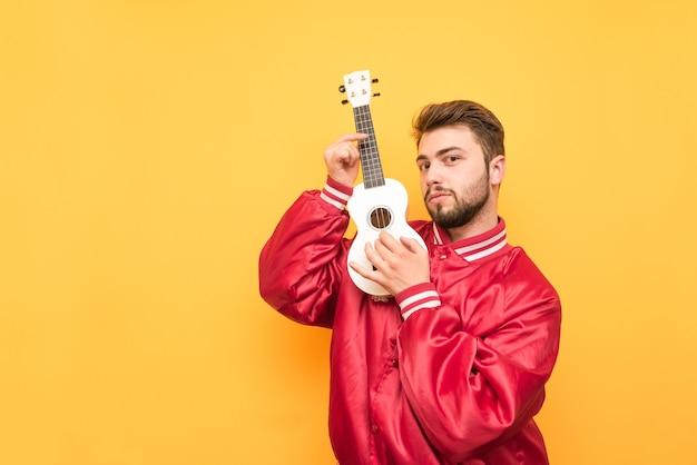 黄色の手にウクレレを持ち、赤いジャケットを着てポーズをとって立っている成人男性の肖像画。 Premium写真