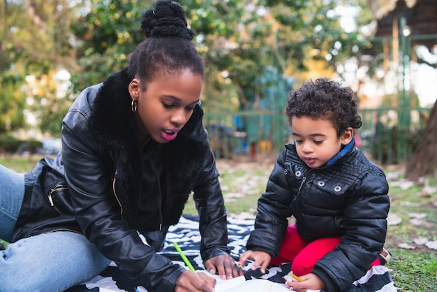 公園で野外で一緒に遊んで楽しんでいる息子を持つアフリカ系アメリカ人の母の肖像画。片親家族。 無料写真