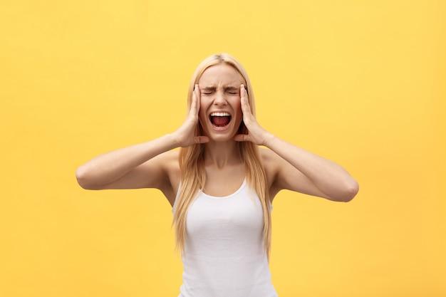 Портрет злой раздраженной женщины с поднятыми руками, крича на камеру, изолированных на желтом фоне Premium Фотографии