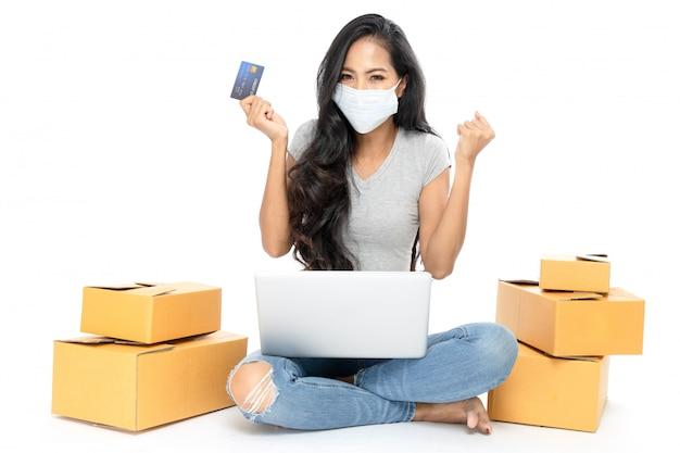 Портрет азиатской женщины сидит на полу с множеством коробок сбоку. у нее есть кредитная карта для покупок в интернете. она носит медицинскую маску от гриппа. изолированные на белом фоне Premium Фотографии