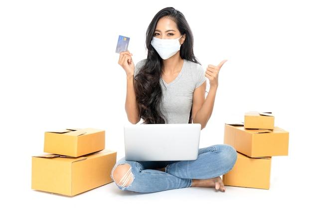 Портрет азиатской женщины сидит на полу с множеством коробок сбоку Premium Фотографии