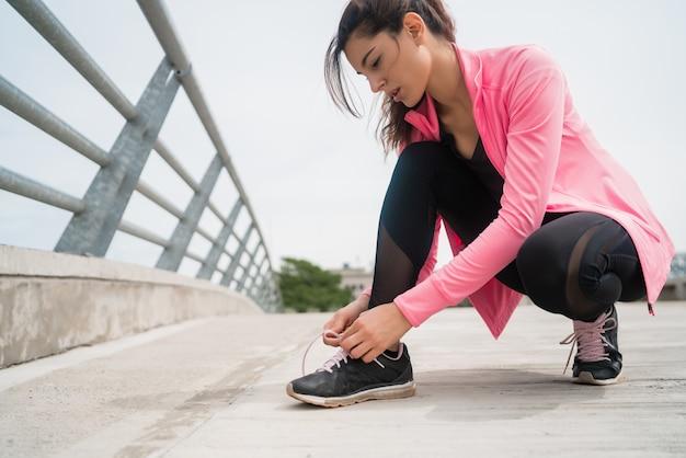 彼女の靴ひもを結び、屋外でジョギングの準備をしている運動女性の肖像画。スポーツと健康的なライフスタイルのコンセプト。 無料写真