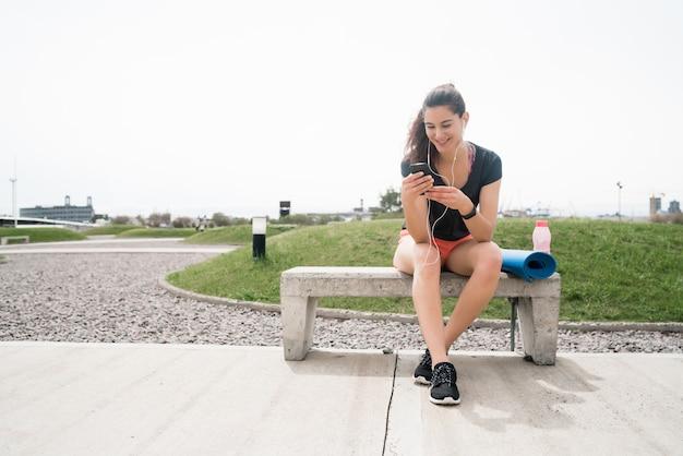 Портрет спортивной женщины, использующей свой мобильный телефон в перерыве от тренировки. спорт и здоровый образ жизни. Бесплатные Фотографии