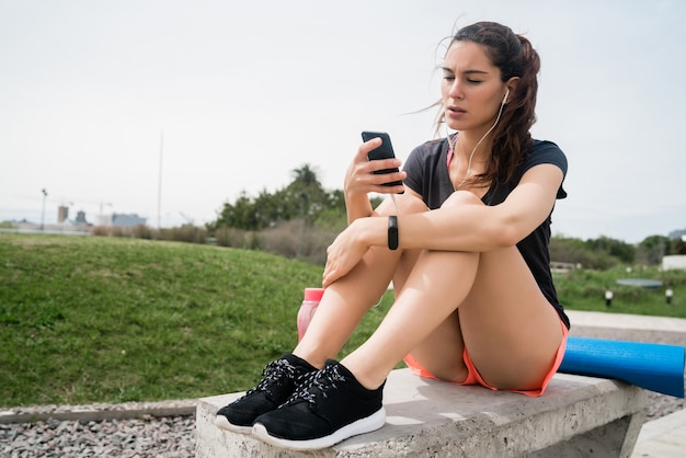 Портрет спортивной женщины, использующей свой мобильный телефон в перерыве от тренировки. спорт и здоровый образ жизни. Premium Фотографии
