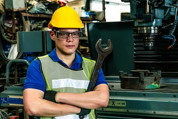 工場でポーズをとるエンジニアの肖像画 Premium写真
