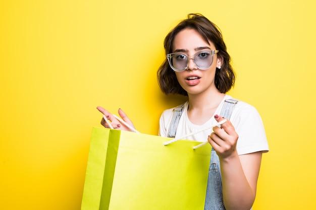 分離された買い物袋を保持しているサングラスを着て興奮している美しい少女の肖像画 無料写真