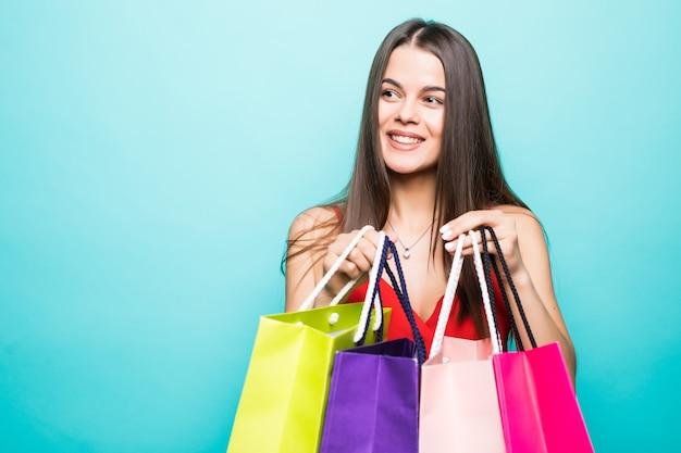 赤いドレスと青い壁に隔離の買い物袋を保持しているサングラスを身に着けている興奮した美しい少女の肖像画 無料写真