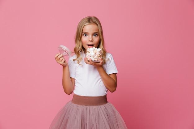 マシュマロの瓶を保持している興奮している女の子の肖像画 無料写真