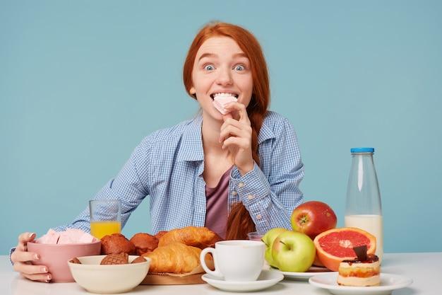 マシュマロを保持し、さまざまな朝食を食べている興奮した赤い髪の女性の肖像画 無料写真