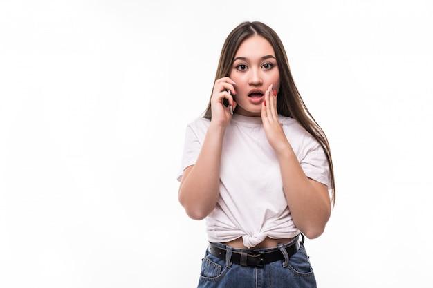 Портрет взволнованной потрясенной азиатской женщины, говорящей по мобильному телефону и жестикулирующей по белой стене Бесплатные Фотографии
