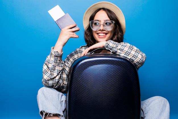 Портрет возбужденной молодой женщины, одетой в летнюю одежду, держит паспорт с билетами на самолет, стоя с изолированным чемоданом Бесплатные Фотографии
