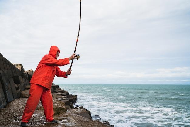 海の岩で釣り老人の肖像画。釣りのコンセプトです。 無料写真