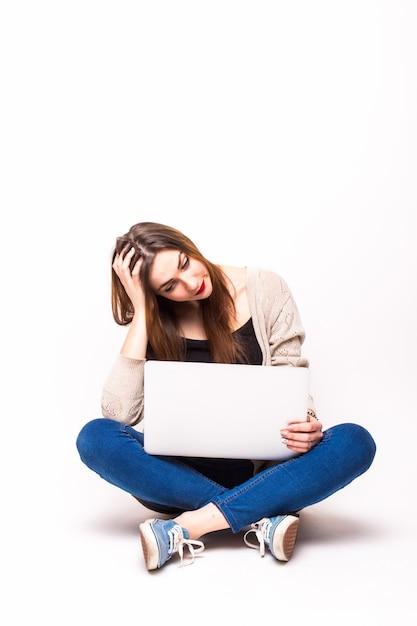 흰색 위에 바닥에 앉아있는 동안 노트북을 들고 탱크 탑을 입은 화가 소녀의 초상화 무료 사진