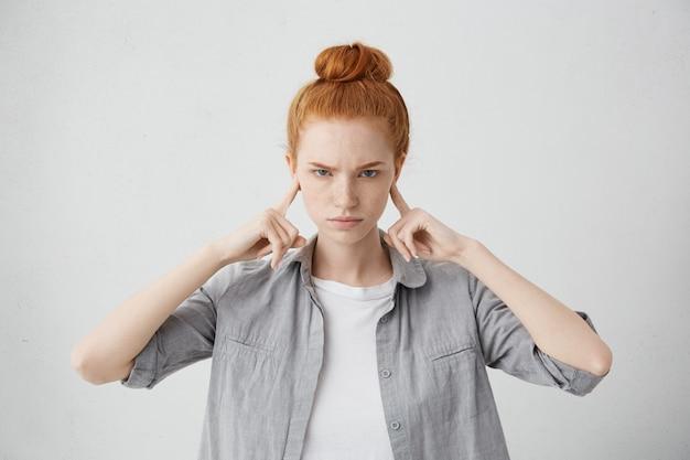 眉をひそめ、耳を指で塞いでいる怒ってイライラする若い女性の肖像画は、大きな音に耐えられず、ストレスの多い不快な状況や対立を無視することもできません。人間の否定的な感情 無料写真