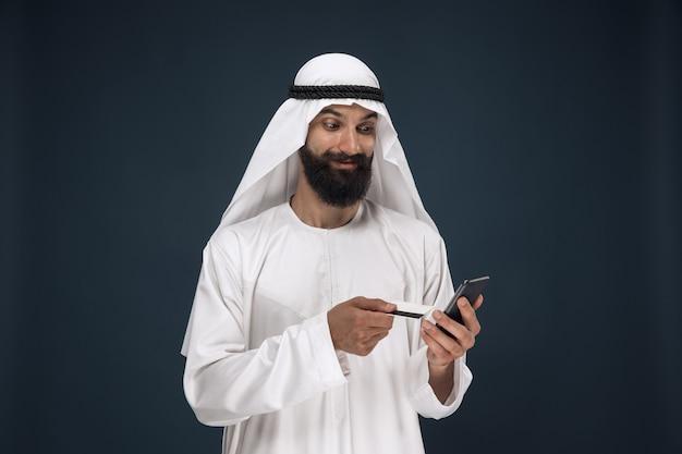 アラビアのサウジアラビアの実業家の肖像画。請求書の支払い、オンラインショッピング、または賭けにスマートフォンを使用している男性。ビジネス、金融、顔の表情、人間の感情の概念。 無料写真