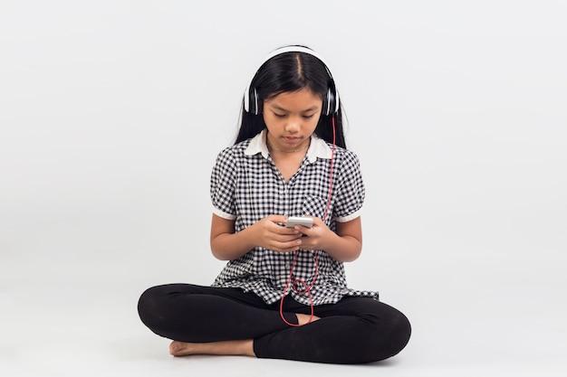 Портрет азиатских детей девушка сидит, слушать музыку изолированные Premium Фотографии