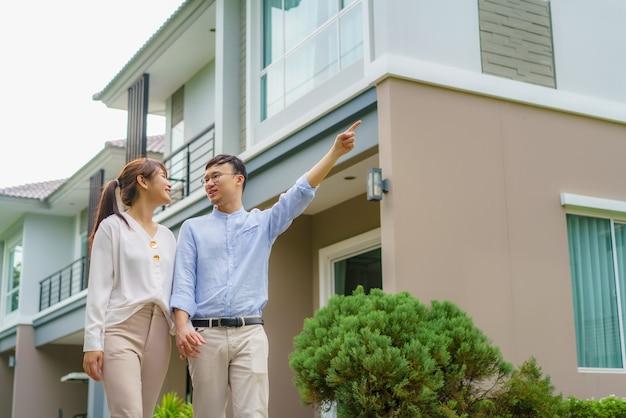 Портрет азиатской пары, идущей и обнимающейся вместе, выглядит счастливой перед своим новым домом, чтобы начать новую жизнь. семья, возраст, дом, недвижимость и люди концепции. Premium Фотографии