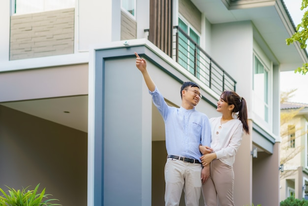 Портрет азиатской пары, идущей, обнимающейся и указывающей вместе, выглядящей счастливой перед их новым домом, чтобы начать новую жизнь. семья, возраст, дом, недвижимость и люди концепции. Premium Фотографии