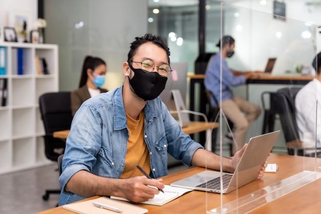 アジアのオフィス従業員のビジネスマンの肖像画は、人種の同僚と新しい通常のオフィスで防護マスクを着用します。社会的距離はコロナウイルスcovid-19を防ぎます。 Premium写真
