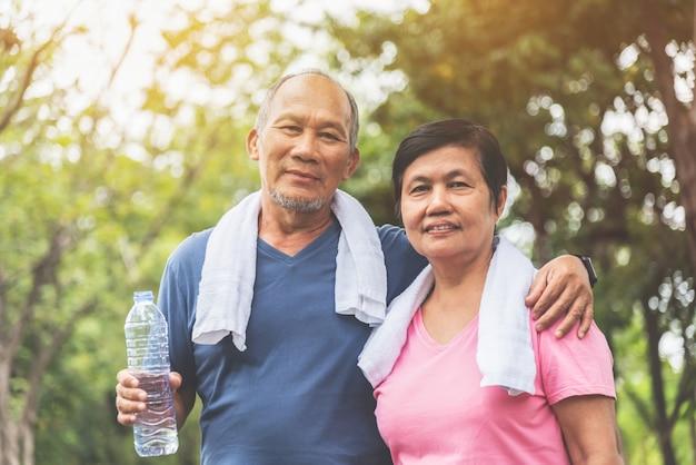Портрет азиатских старших пар в голубой и розовой рубашке усмехаясь и стоя на парке внешнем. Premium Фотографии