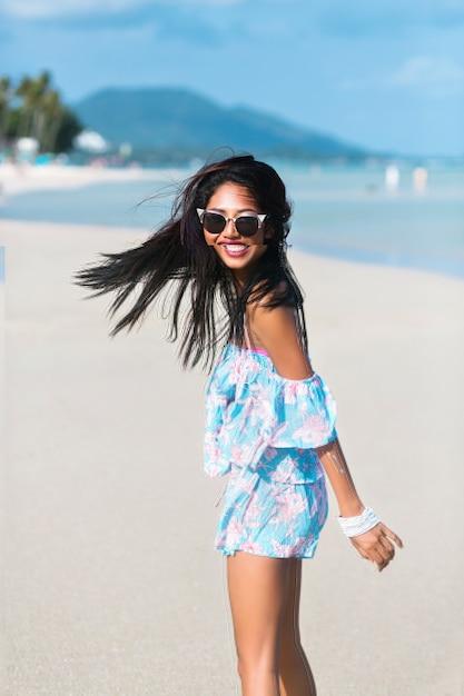 Портрет азиатской тайской девушки в солнечных очках и цветочном платье, развлекающейся на тропическом пляже Бесплатные Фотографии