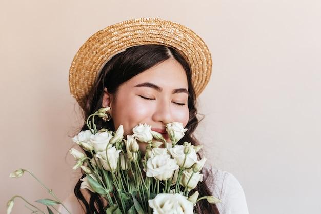 目を閉じて花を嗅ぐ麦わら帽子のアジアの女性の肖像画。白いトルコギキョウの花束を持っている美しい日本人女性のスタジオショット。 無料写真