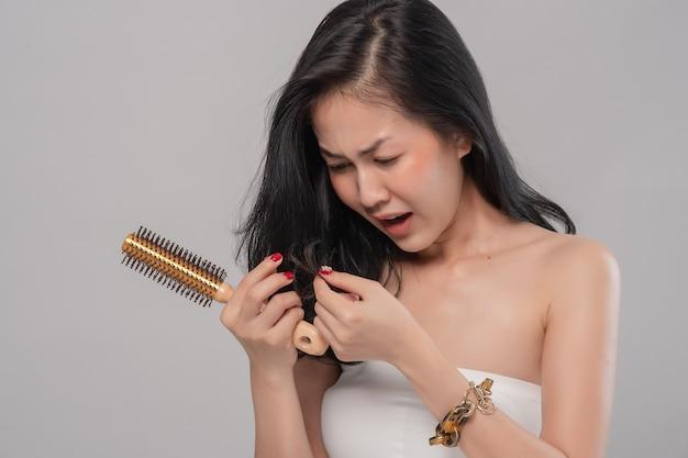 Портрет азиатской женщины с длинными волосами с расческой и проблемными волосами на сером Premium Фотографии