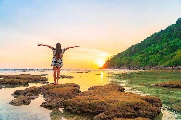 休暇中の海の周りの日没で腕を開いて岩の上のアジアの女性の肖像画 無料写真