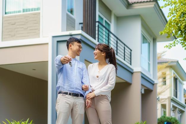 Портрет азиатской молодой пары, стоящей и обнимающейся вместе и держащей ключ от дома, счастливой перед своим новым домом, чтобы начать новую жизнь. семья, возраст, дом, недвижимость и люди концепции. Premium Фотографии