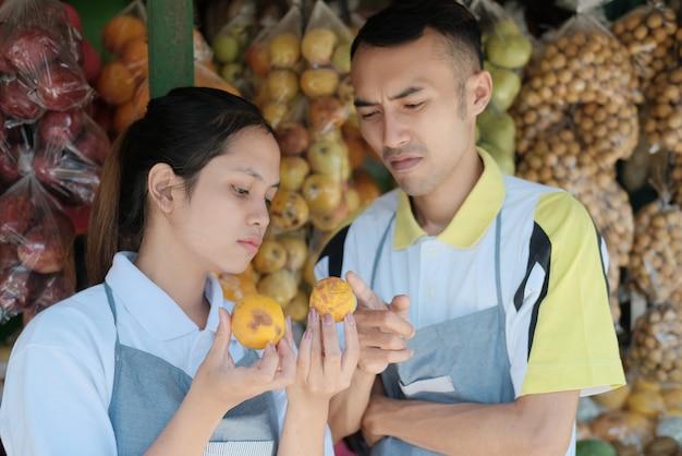 の屋台の果物で果物を分類しながら柑橘系の果物を選択するアシスタントショップのカップルの肖像画 Premium写真
