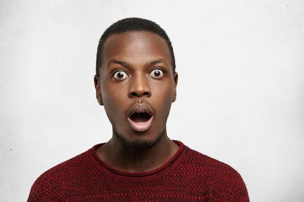 Портрет изумленного молодого человека афроамериканца с косоглазым взглядом, одетого небрежно, с открытым ртом и отвисшей челюстью, не может поверить шокирующим новостям Бесплатные Фотографии