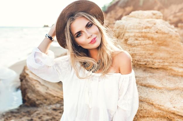 Портрет привлекательной блондинки с длинными волосами, позирует на безлюдном пляже. она улыбается в камеру. Бесплатные Фотографии