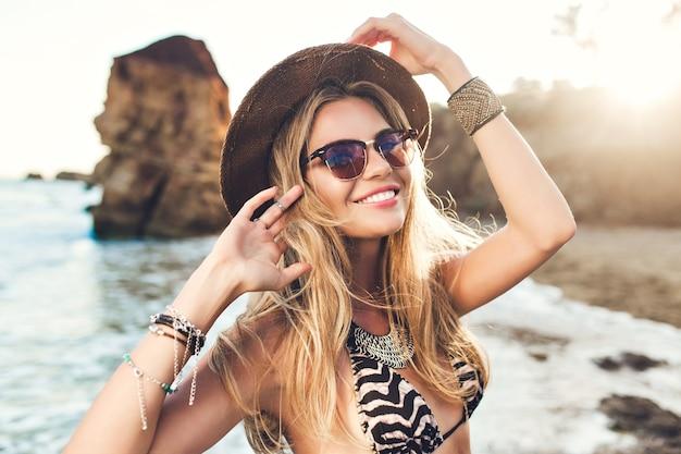Портрет привлекательной белокурой девушки с длинными волосами, позирующими на скалистом пляже. она улыбается. Бесплатные Фотографии