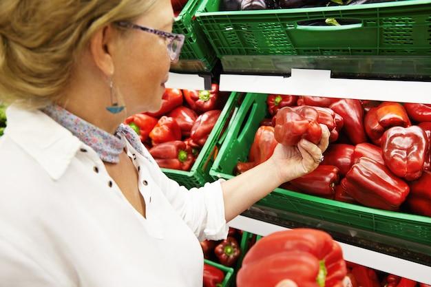 식료품 점 또는 슈퍼마켓의 생산 부서에서 과일과 야채를 쇼핑하는 매력적인 여성 연금 수급자의 초상화, 가족 저녁 식사를위한 큰 고추 따기, 최고의 것을 선택 무료 사진