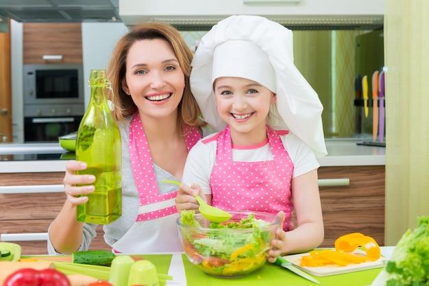 キッチンでサラダを調理する魅力的な幸せな母と娘の肖像画。 無料写真