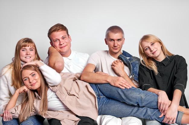 白い背景で隔離のスタジオフロアで魅力的なスタイリッシュな若者の肖像画 Premium写真