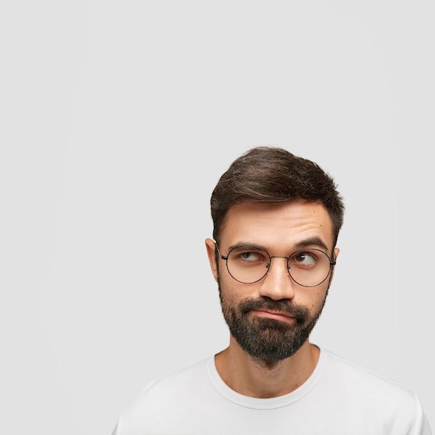 魅力的な無精ひげを生やした男の肖像画は、考えを深くして、戸惑いを脇に置いて見えます 無料写真