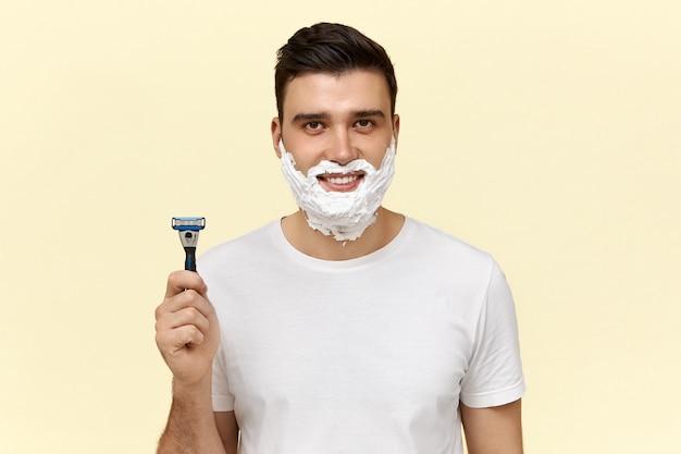 使い捨てのかみそりを持って、彼の顔にシェービングクリームでポーズをとるカジュアルなtシャツの魅力的な若い黒髪の男の肖像画 無料写真
