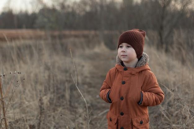 Портрет привлекательного молодого человека, улыбающегося и смотрящего в камеру в поле Premium Фотографии