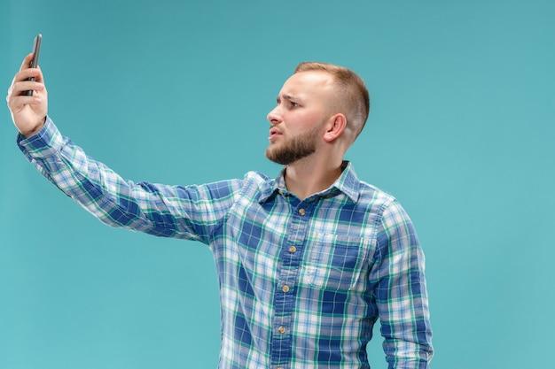 彼のスマートフォンでselfieを取る魅力的な若い男の肖像 無料写真