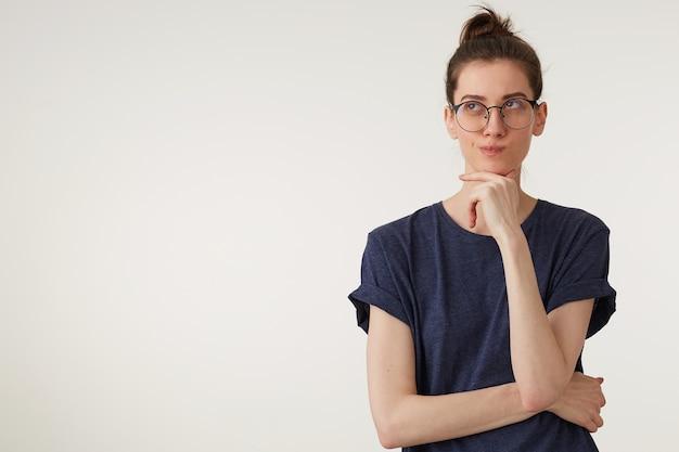 Портрет привлекательной молодой женщины в очках смотрит вверх, обдумывает мысль или идею, вдумчивый, держит кулак возле подбородка, носит повседневную футболку на белом фоне Бесплатные Фотографии