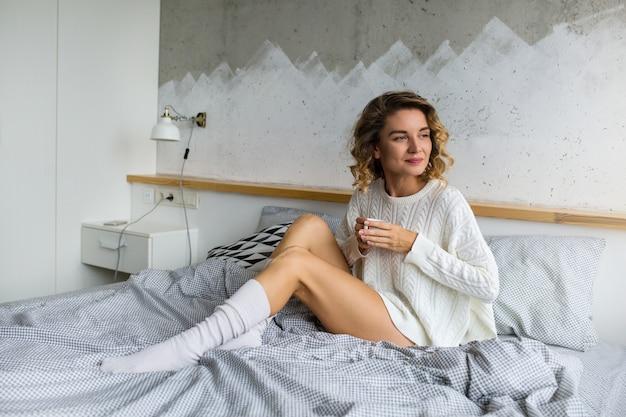 朝はベッドに座って、カップでコーヒーを飲みながら魅力的な若い女性の肖像画 無料写真